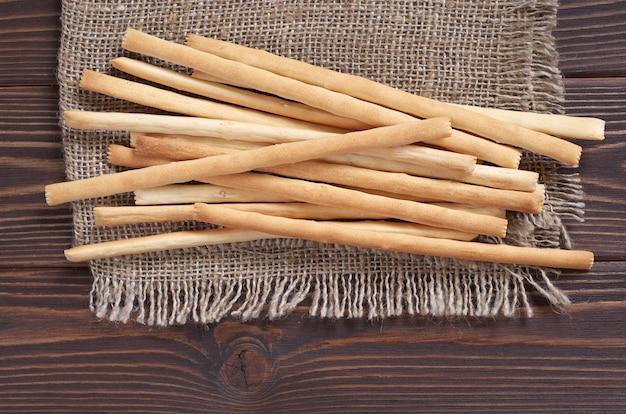 Pilha de palitos de pão na serapilheira está localizada em fundo de madeira marrom