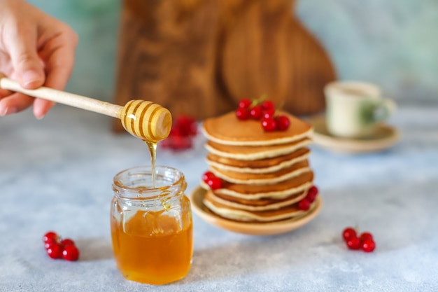 Pilha de panquecas caseiras com calda de mel e frutas.