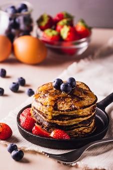 Pilha de panquecas caseiras com mirtilos e morangos, perfeitas para o café da manhã