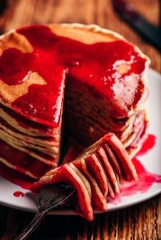 Pilha de panquecas com geléia de frutas vermelhas em um prato branco sobre a mesa de madeira