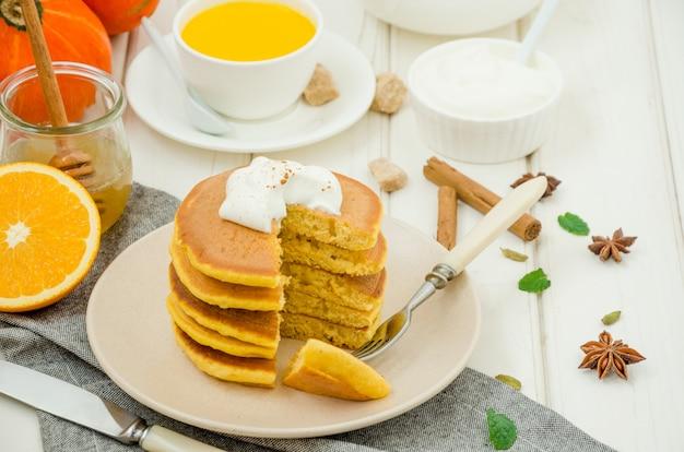 Pilha de panquecas de abóbora picantes em um prato com mel e chantilly em uma superfície de madeira branca