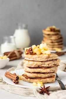 Pilha de panquecas de maçã deliciosa com maçãs caramelizadas fritas e especiarias.