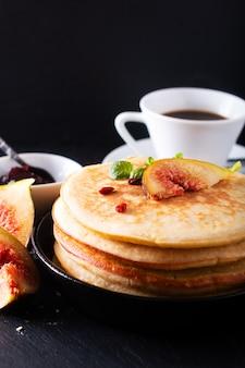 Pilha de panquecas orgânicas caseiras com café da manhã figo no preto