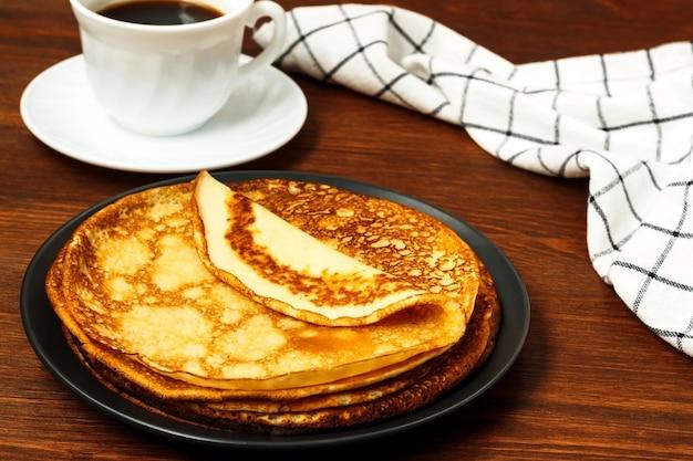 Pilha de panquecas russas finas feitas para encolher com xícara de café e pano de cozinha na mesa de madeira