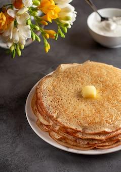 Pilha de panquecas russas quentes blini com manteiga e creme de leite em uma panela. maslenitsa tradicional russo