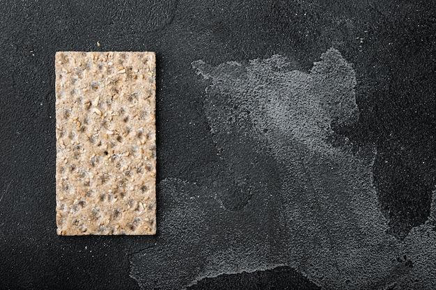Pilha de pão crocante integral com girassol e sementes de gergelim, em uma mesa de pedra preta escura
