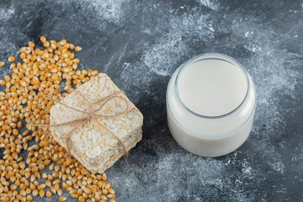 Pilha de pão estaladiço e copo de leite no mármore.