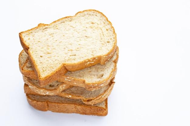 Pilha de pão integral fatiado em fundo branco.