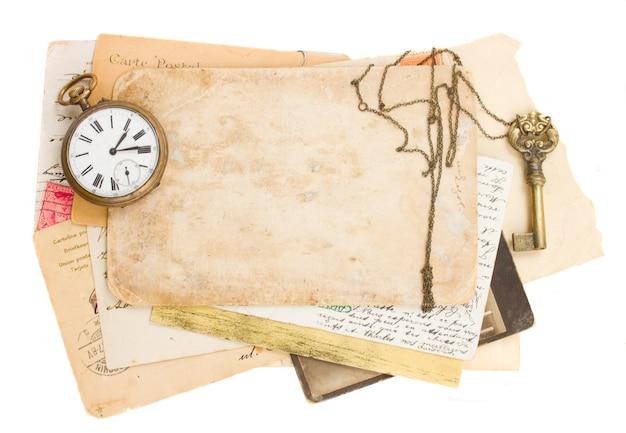 Pilha de papéis velhos com relógio antigo e chave isolada no fundo branco