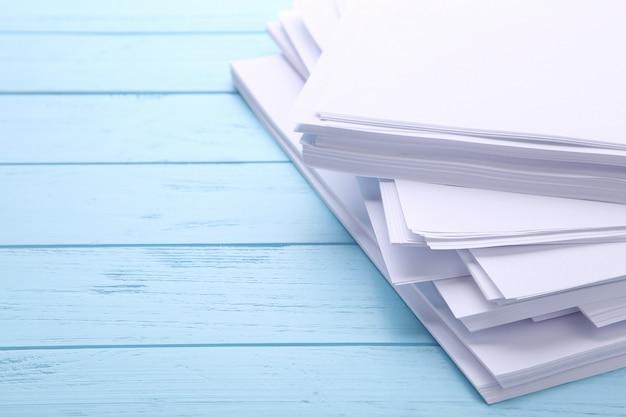 Pilha de papel branco em madeira azul