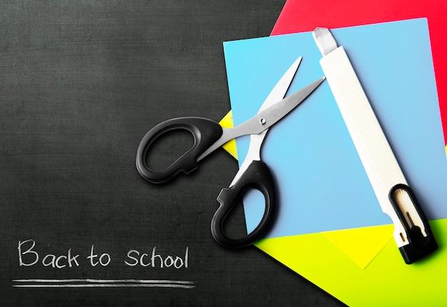 Pilha de papel colorido com tesoura e cortador com fundo preto. conceito de volta às aulas