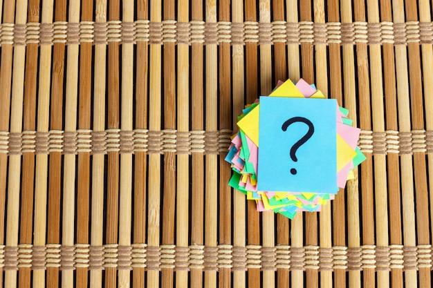 Pilha de papel de ponto de interrogação no conceito de mesa para confusão