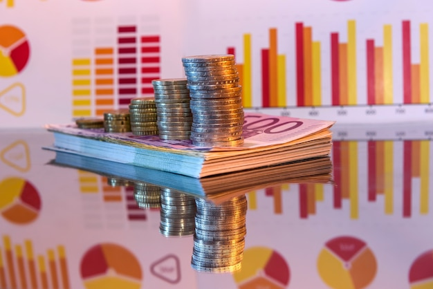 Pilha de papel euro e moedas com reflexo