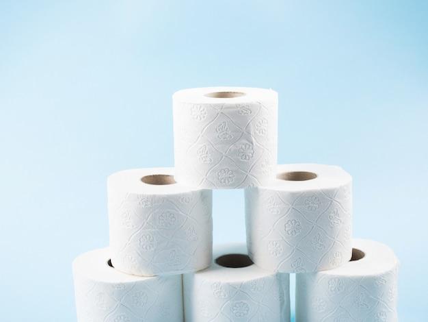 Pilha de papel higiênico rola no pano de fundo azul