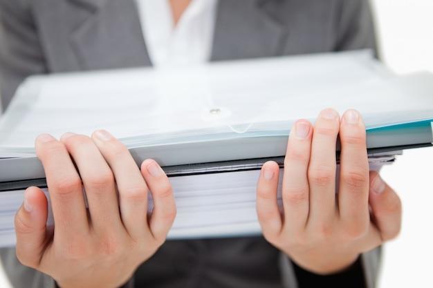 Pilha de papelada sendo realizada por mãos femininas