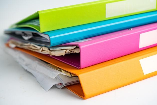 Pilha de pasta de arquivo fichário de várias cores na mesa no escritório de negócios.