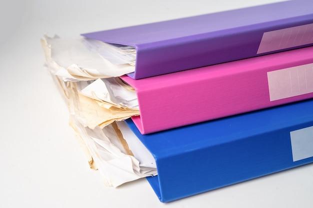 Pilha de pasta de arquivo fichário de várias cores na mesa no escritório.