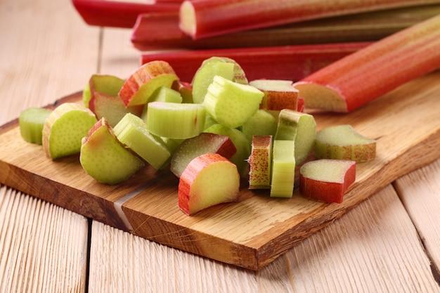Pilha de pedaços recém cortados de ruibarbo azedo em uma placa de madeira na mesa. planta cultivada, que é consumida como fruta após o cozimento.
