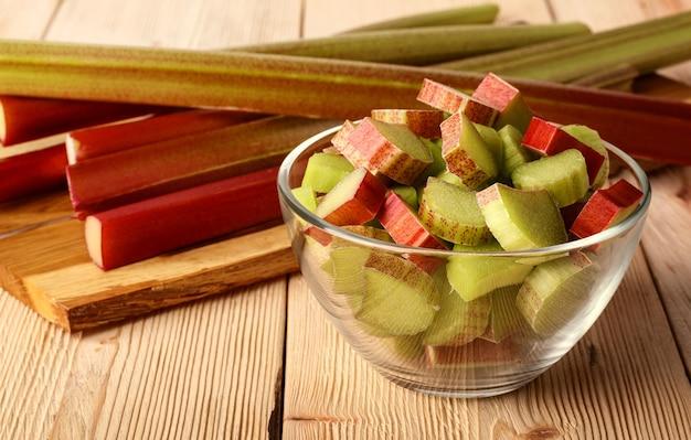 Pilha de pedaços recém cortados de ruibarbo azedo em uma tigela de vidro sobre uma mesa de madeira. planta cultivada, que é consumida como fruta após o cozimento.