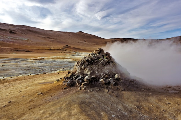 Pilha de pedra em hverir, na islândia, com fontes de enxofre, fumarolas e lama como atividade geotérmica.