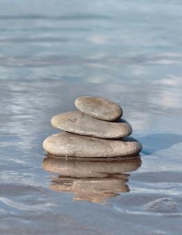 Pilha de pedras cinza no mar com reflexo na água