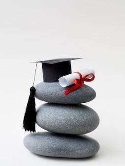 Pilha de pedras com chapéu de formatura e diploma