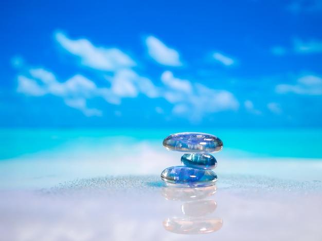 Pilha de pedras de seixo e plumeria na praia numa superfície de madeira. conceito zen, spa, verão, praia, mar, relaxe.