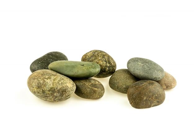 Pilha de pedras e de seixos diferentes isolados no fundo branco.