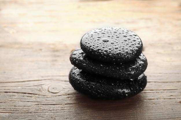 Pilha de pedras quentes do spa na mesa de madeira