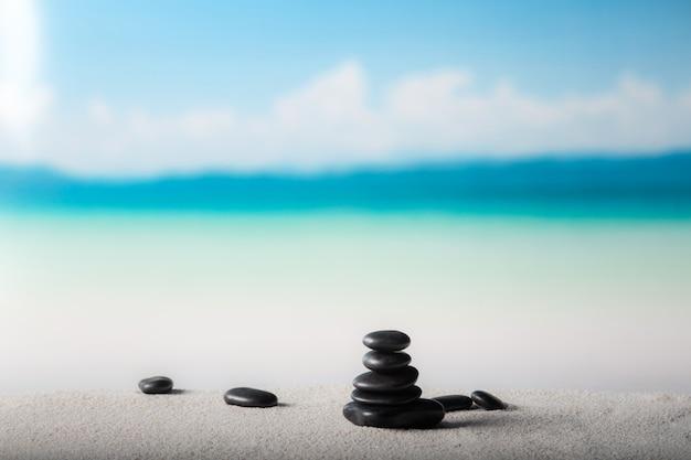 Pilha de pedras zen na praia de areia