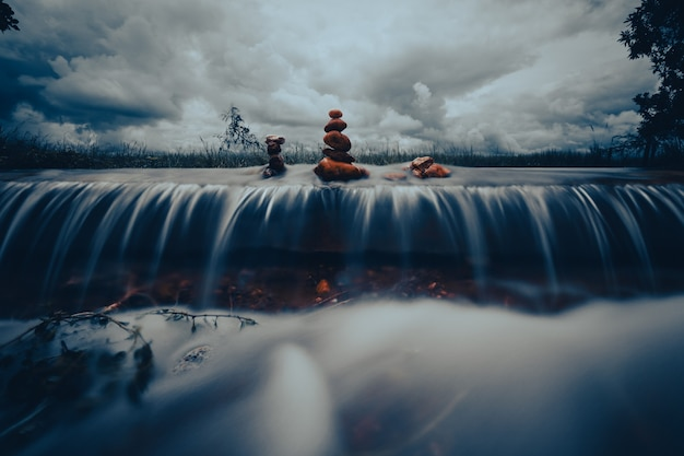 Pilha de pedras zen sobre a cachoeira em fundo de tempestade de nuvens. tom de cor cinematográfica