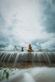 Pilha de pedras zen sobre a cachoeira no fundo da tempestade de nuvens