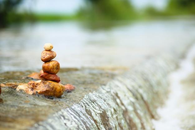 Pilha de pedras zen sobre cachoeira