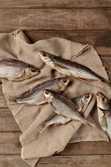 Pilha de peixe salgado seco ao ar em saco com fundo de madeira