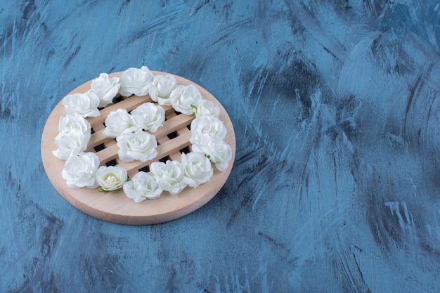 Pilha de pequenas flores brancas colocadas em azul.