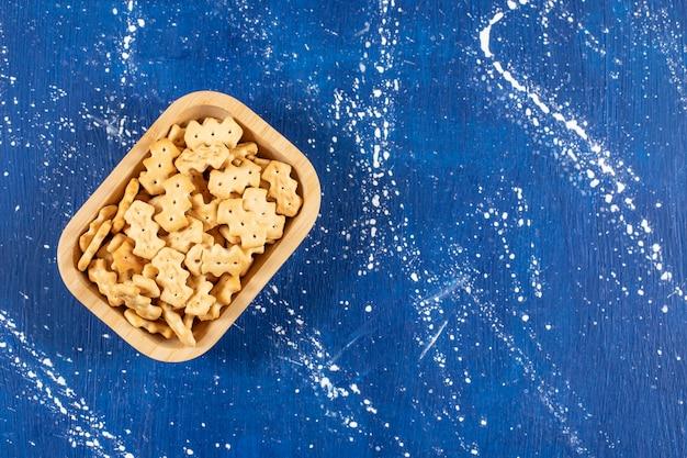 Pilha de pequenos biscoitos salgados colocados em uma tigela de madeira.