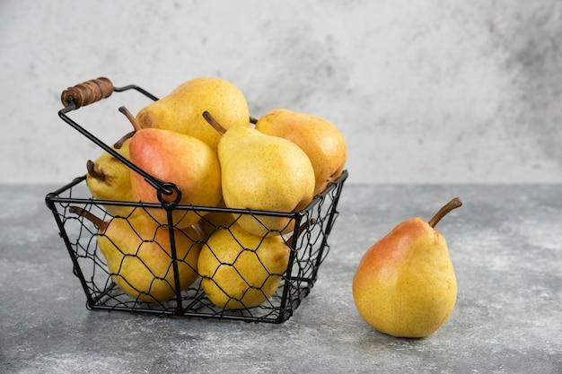 Pilha de peras frescas amarelas em balde de metal na superfície de mármore.