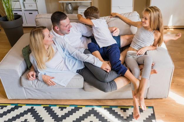 Pilha de pessoas sentadas no mesmo sofá