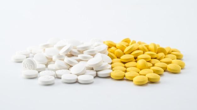 Pilha de pílulas brancas e amarelas sobre fundo branco