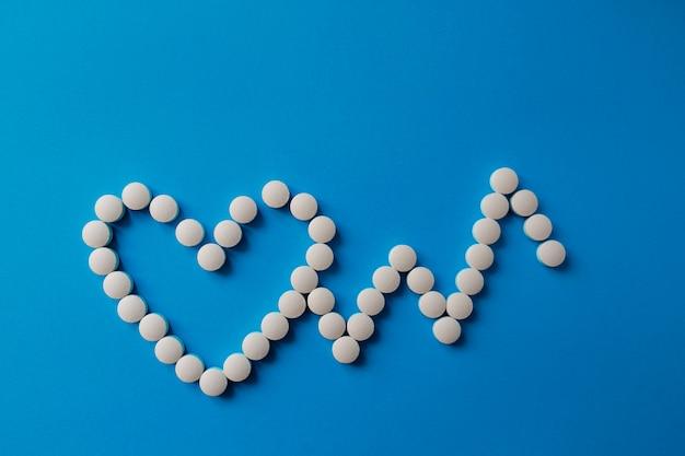 Pilha de pílulas em azul pílulas sortidas de medicamentos farmacêuticos, comprimidos e cápsulas e frasco em azul