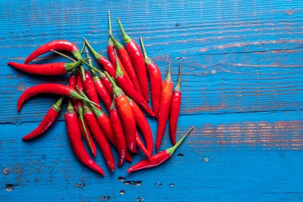 Pilha de pimentas quentes do pimentão no fundo de madeira azul.