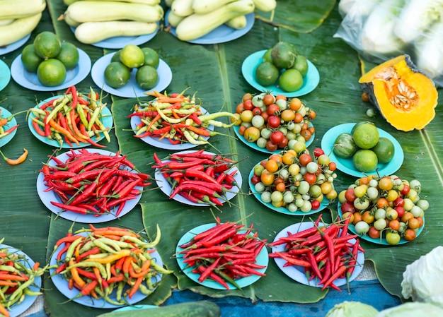 Pilha de pimentões vermelhos e de legumes frescos na placa para a venda no mercado.