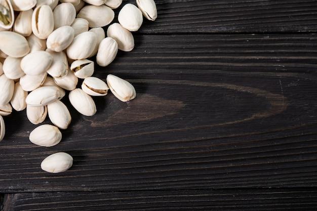 Pilha de pistache em close-up da casca em uma mesa de madeira. foco seletivo