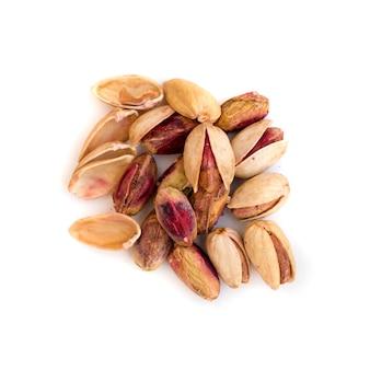 Pilha de pistache inshell e pistachios pelados em fundo branco
