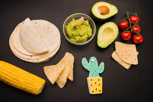 Pilha de pita perto de legumes e molho de guacamole com nachos