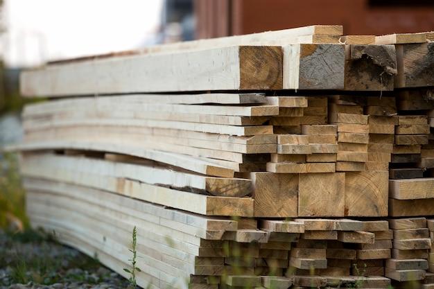 Pilha de placas de madeira ásperas desiguais marrons naturais no terreno de construção.