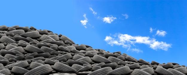 Pilha de pneus de borracha usados com mais de luz no fundo do céu azul