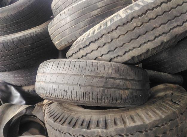 Pilha de pneus de carros usados no pátio da oficina de reparação de pneus