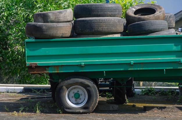 Pilha de pneus usados em uma caminhonete com um pneu furado
