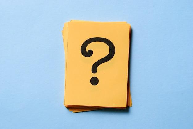 Pilha de pontos de interrogação em cartões amarelos